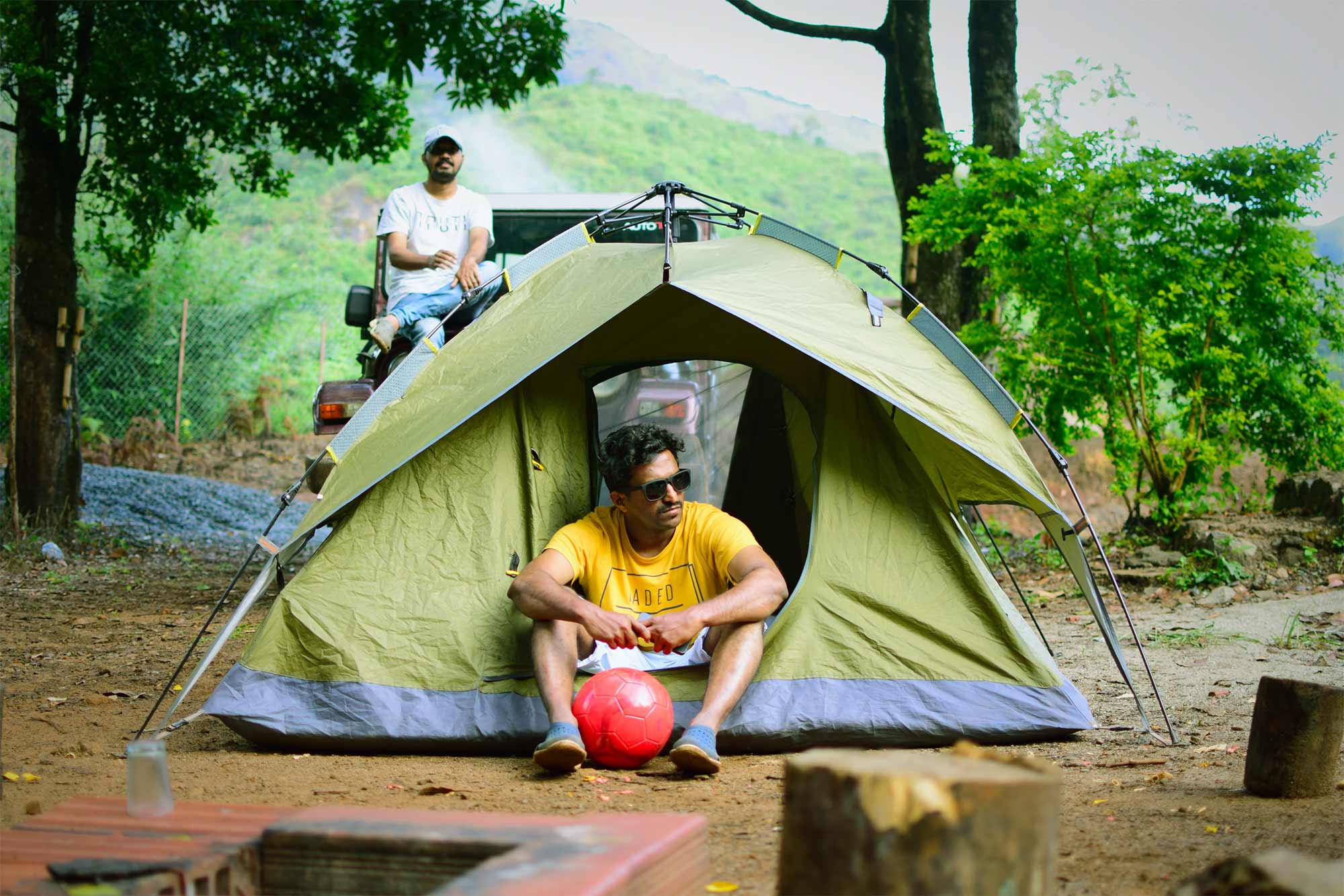 Two guys hanging out at a campsite by a tent