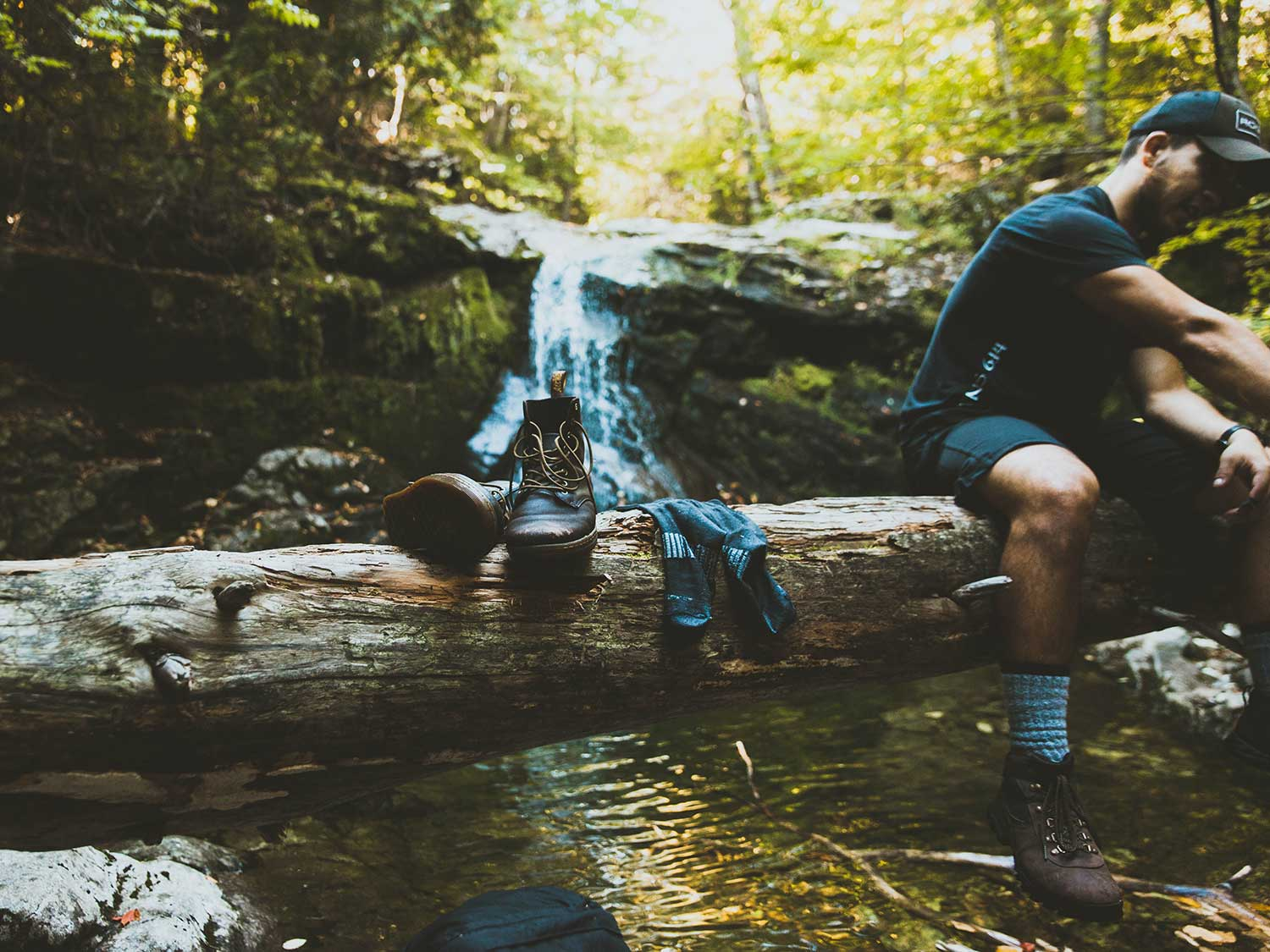 Man sitting on log over river with hiking socks and boots.