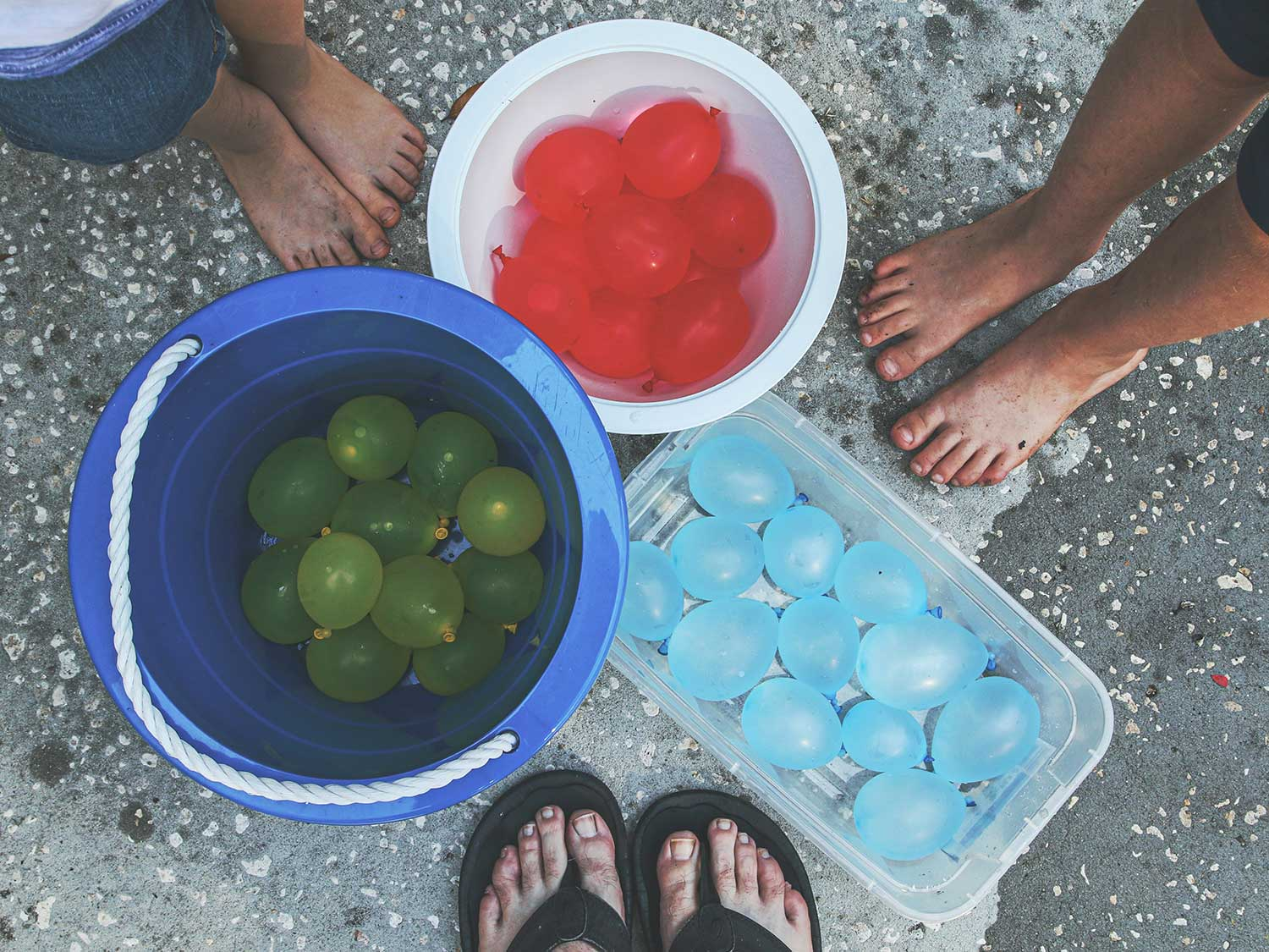 Standing over buckets of water balloons.