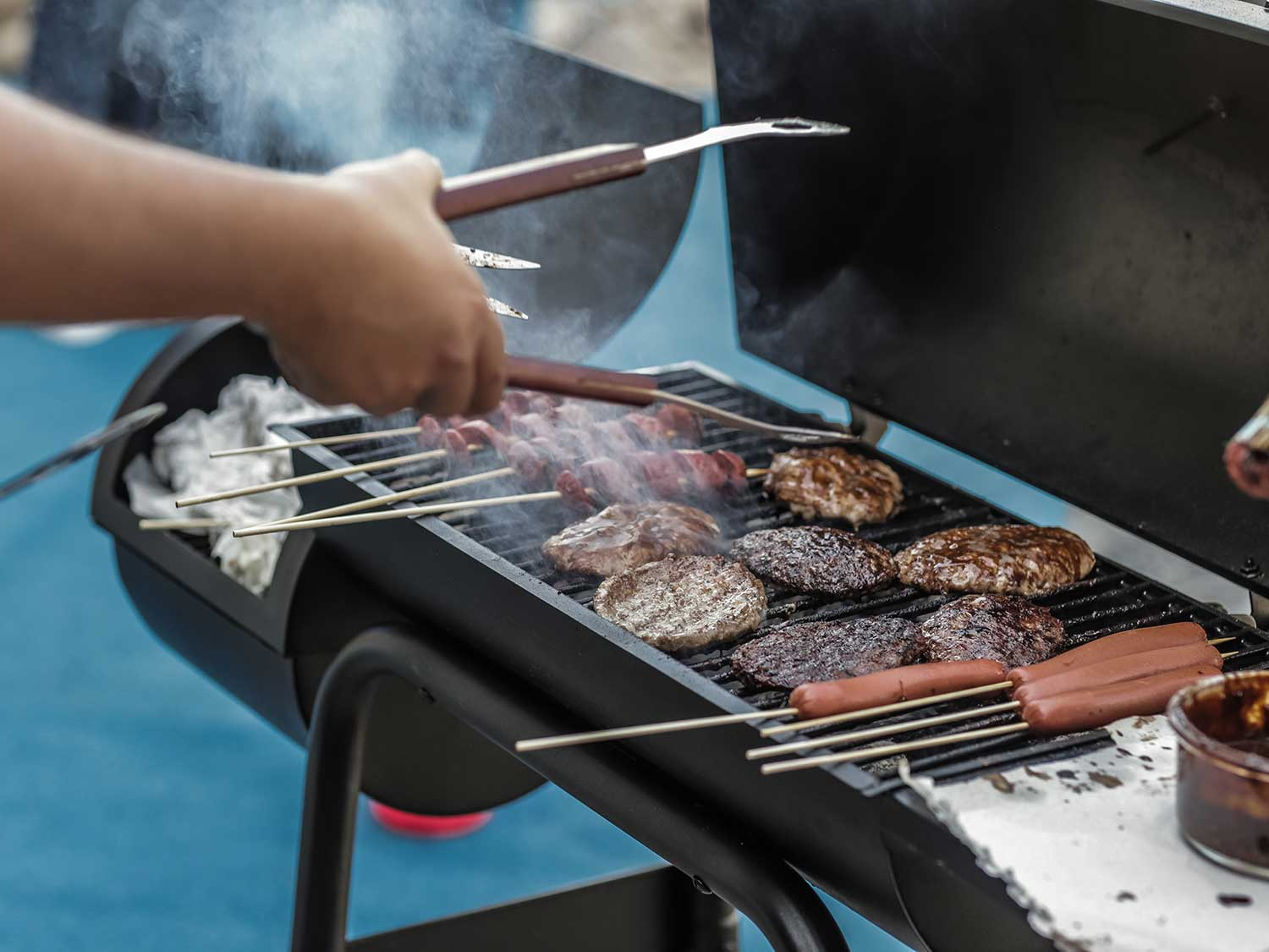 Grilling hamburgers and hotdogs on the barbecue grill.