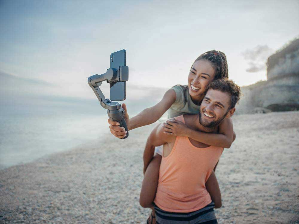 woman and man taking seflie on smart phone stabilizer