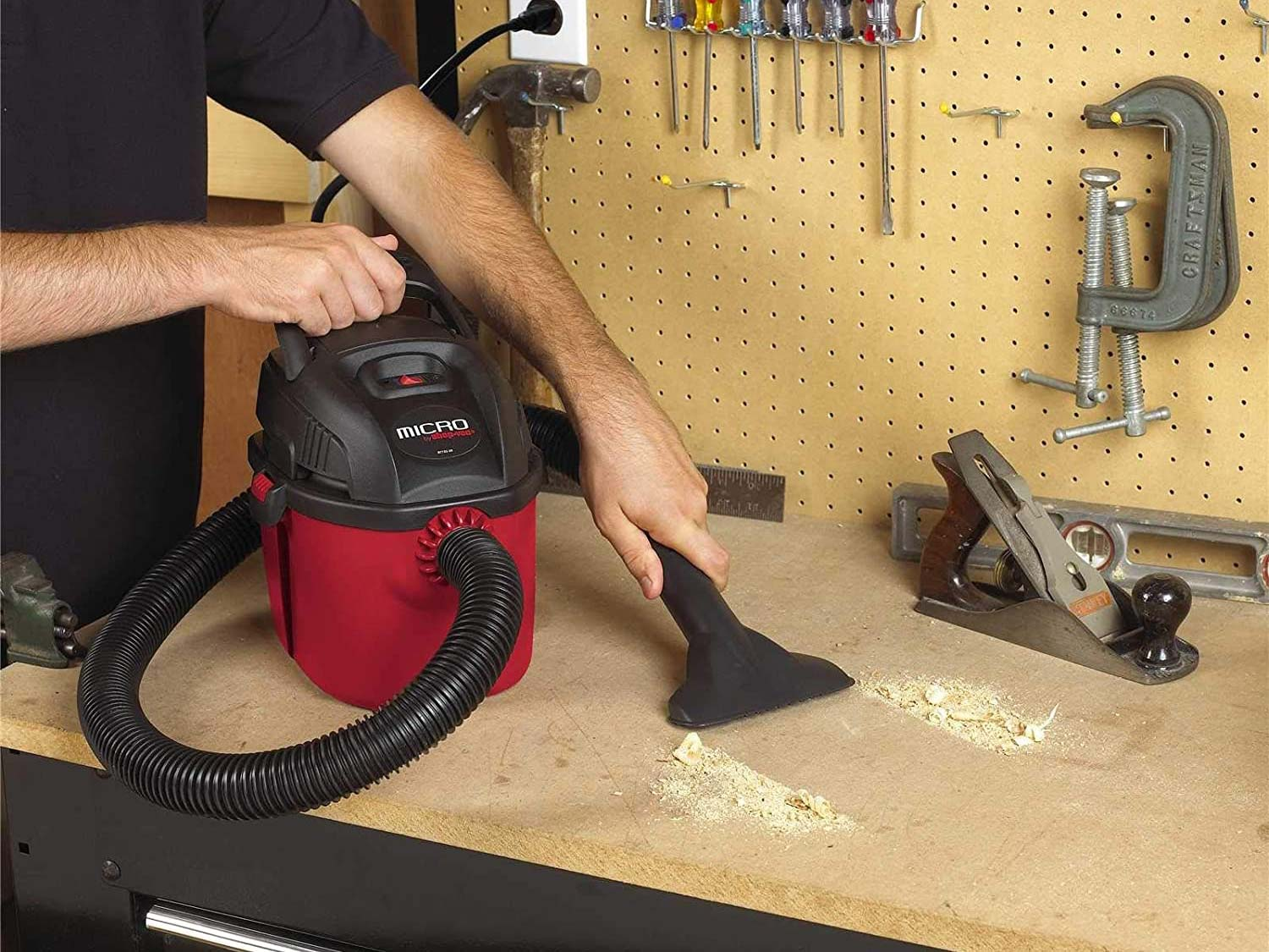 Person using a Shop Vac in a garage