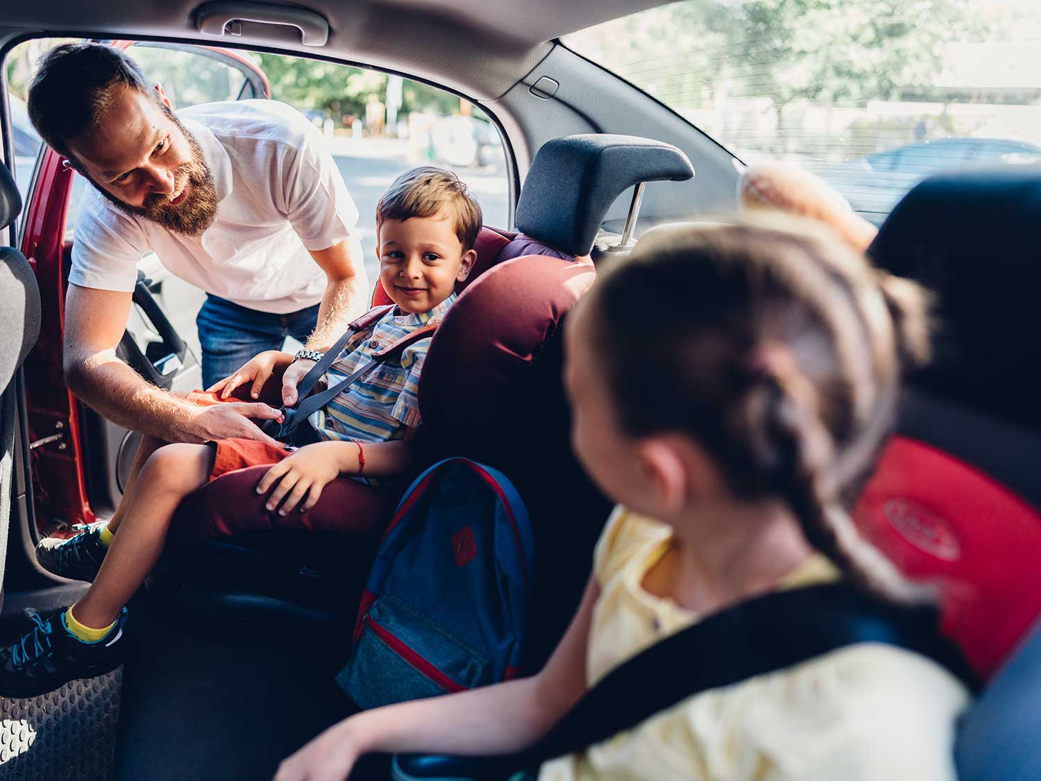Dad and kids in the backseat of a car.