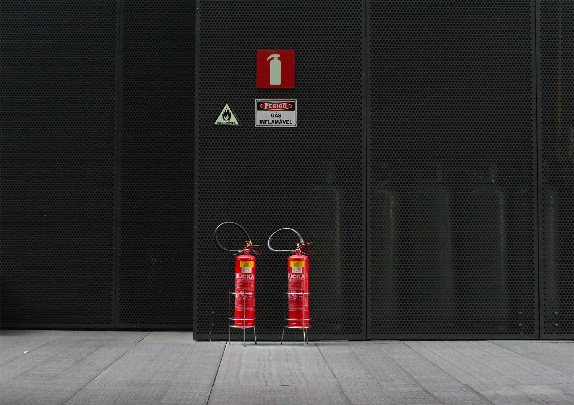 Two fire extinguishers in front of a black wall.
