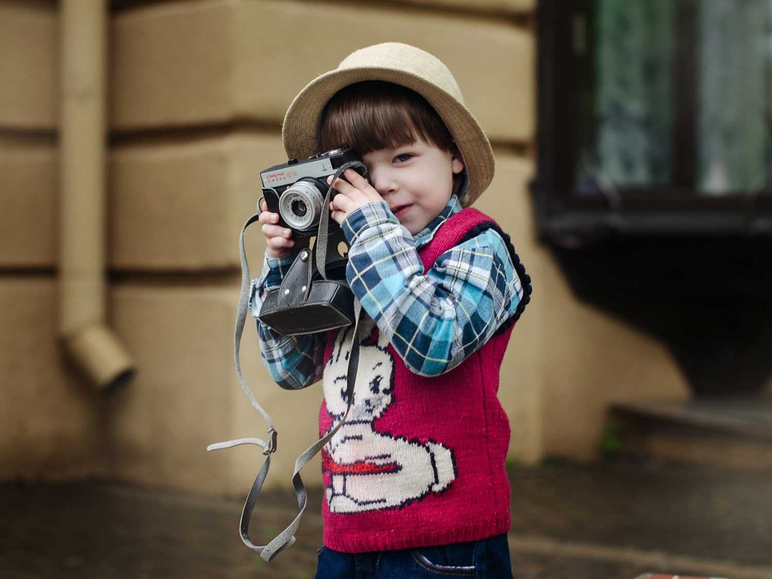 Kid taking a picture with camera.