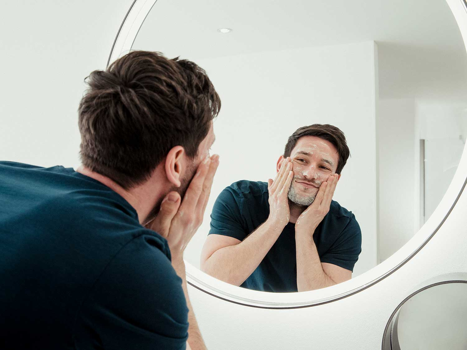 Man washing face with anti-aging-serum.