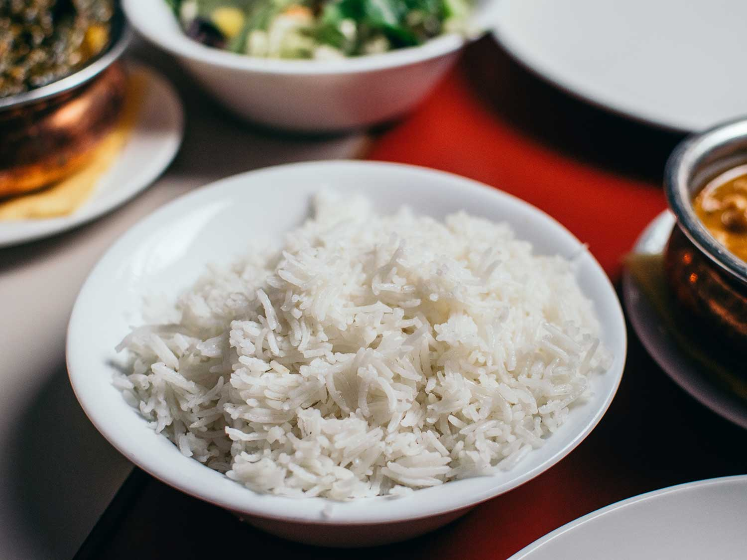 Cooked rice in bowl with other food.