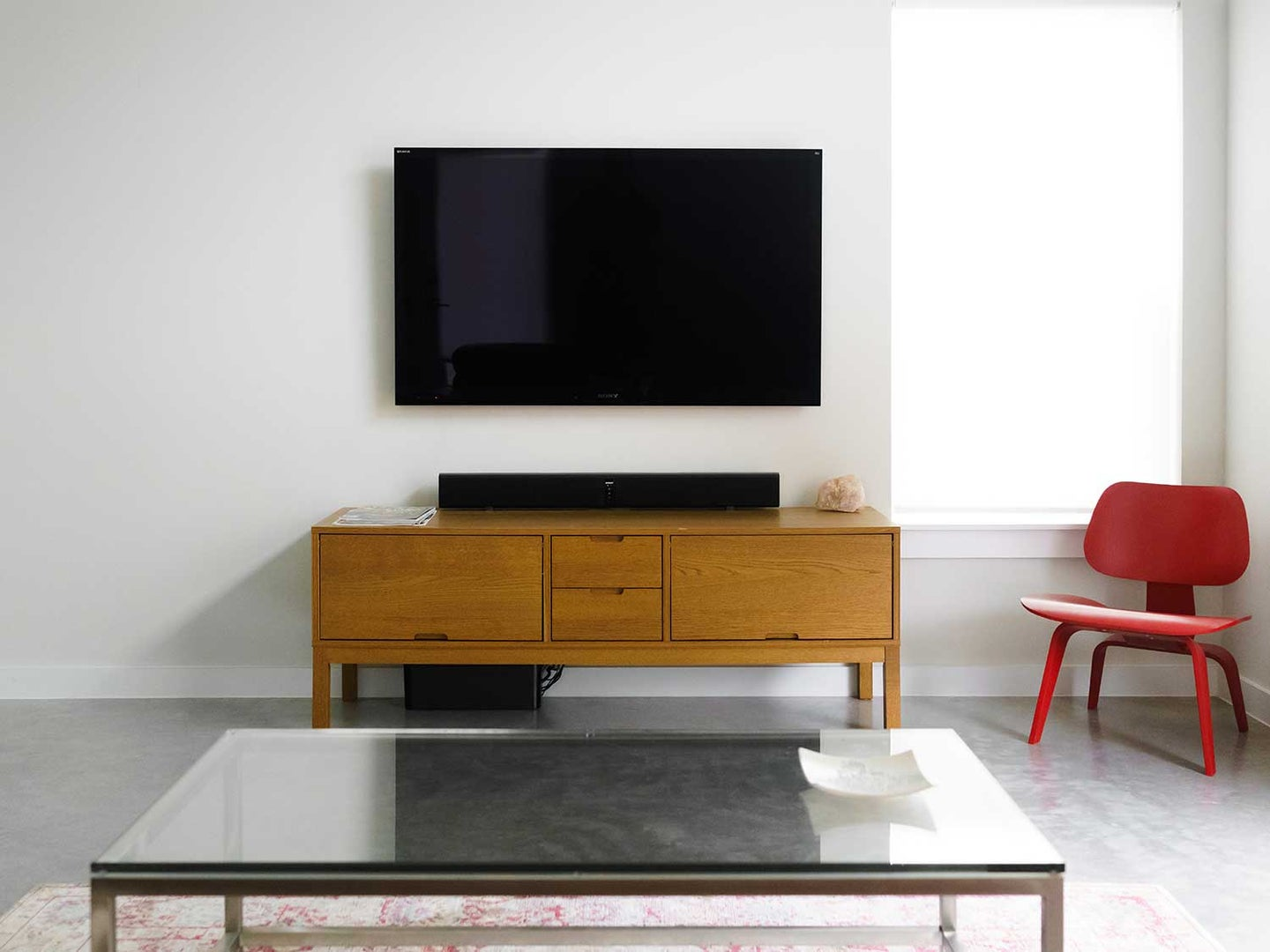 Wall-mounted TV in living room with entertainment center, coffee table, and chair.