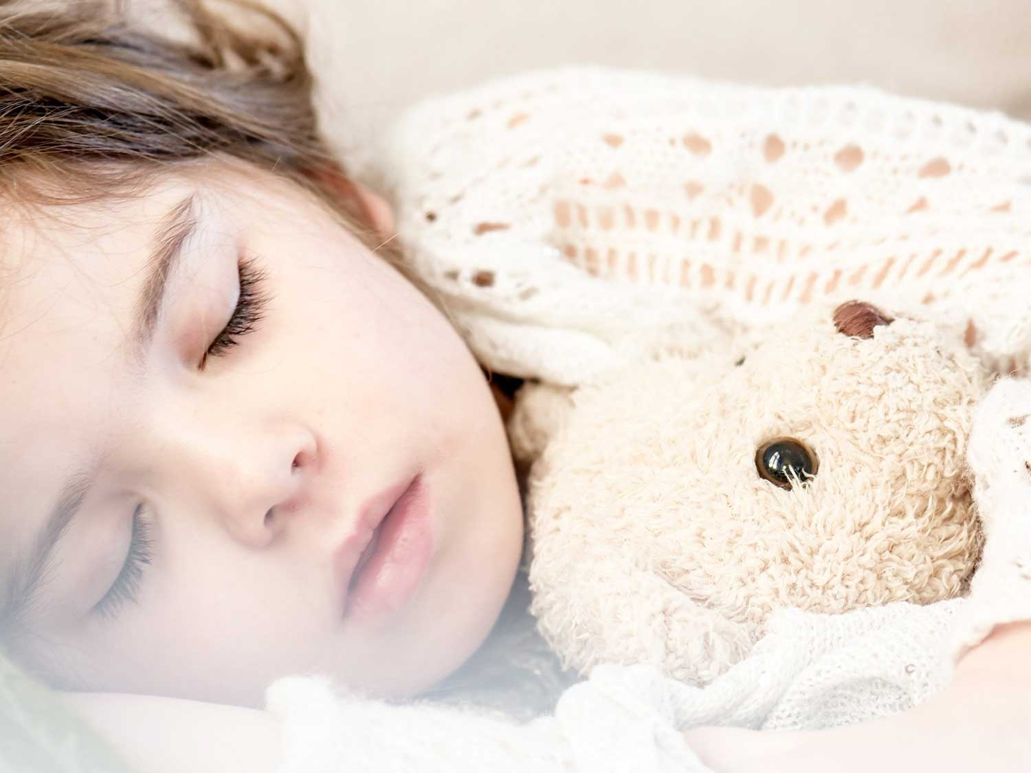Girl napping with pillow and stuffed bear.