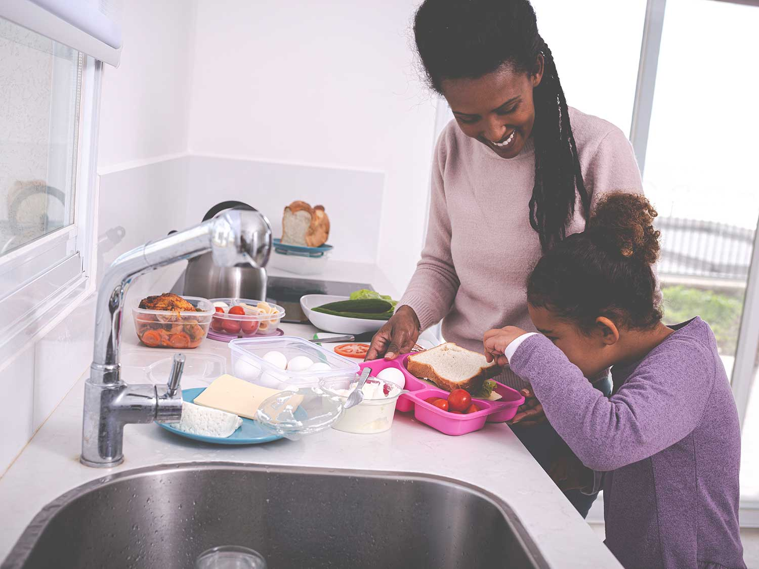 Mother and daughter packing lunch in kid's bento box.