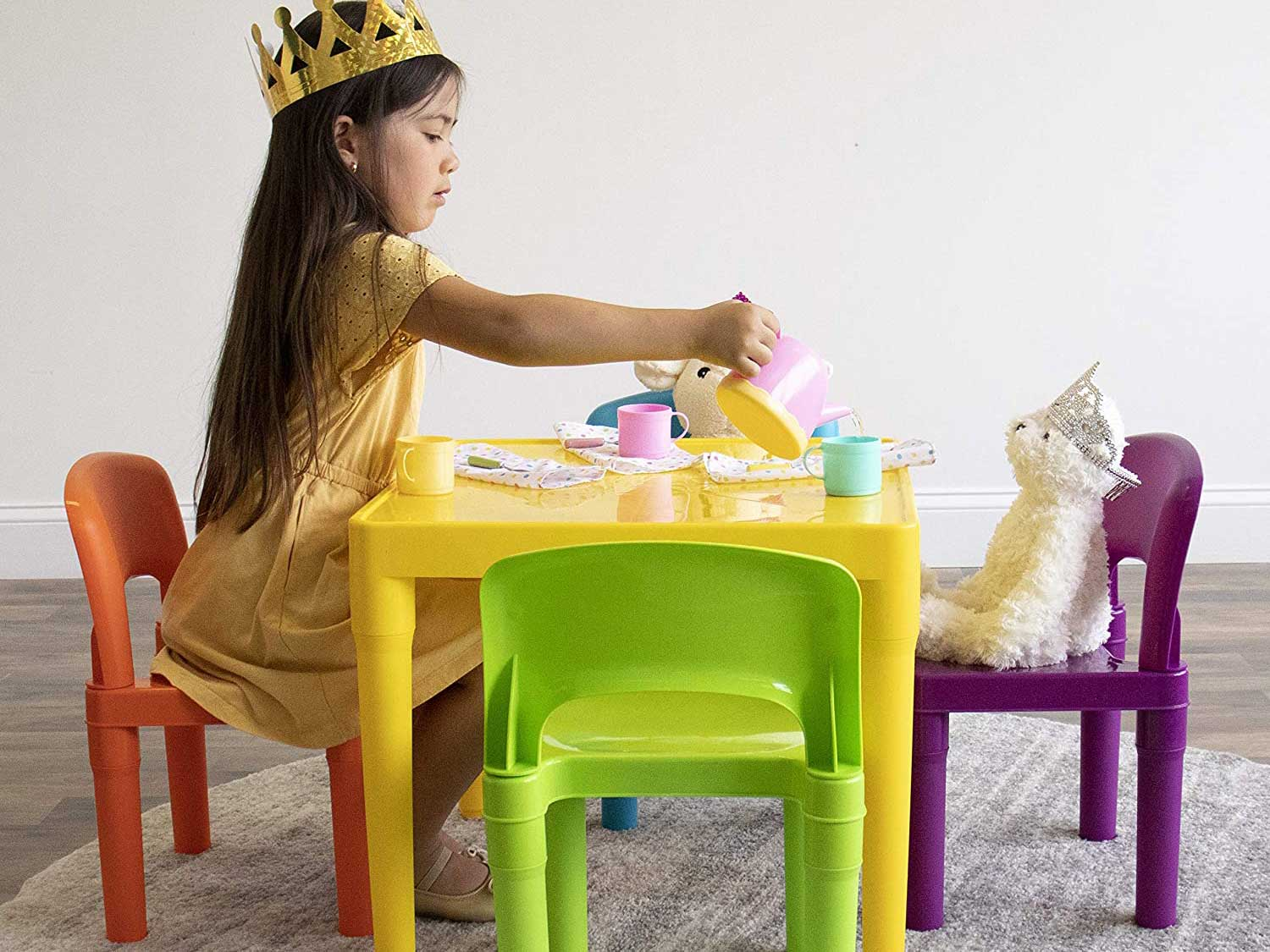 Toddler having tea party with table and chair set and stuffed animals.