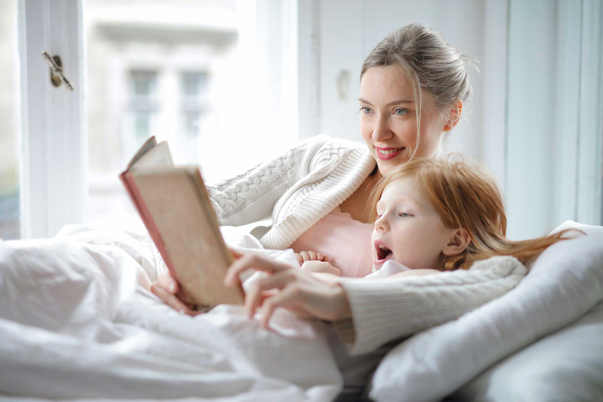 Mother and daughter lying under blanket reading a book