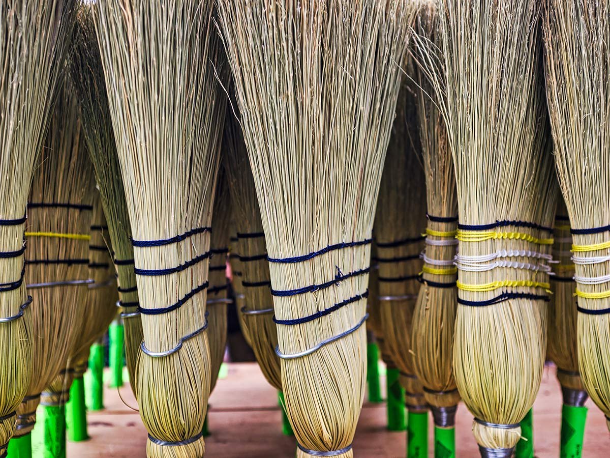 a stand of straw brooms