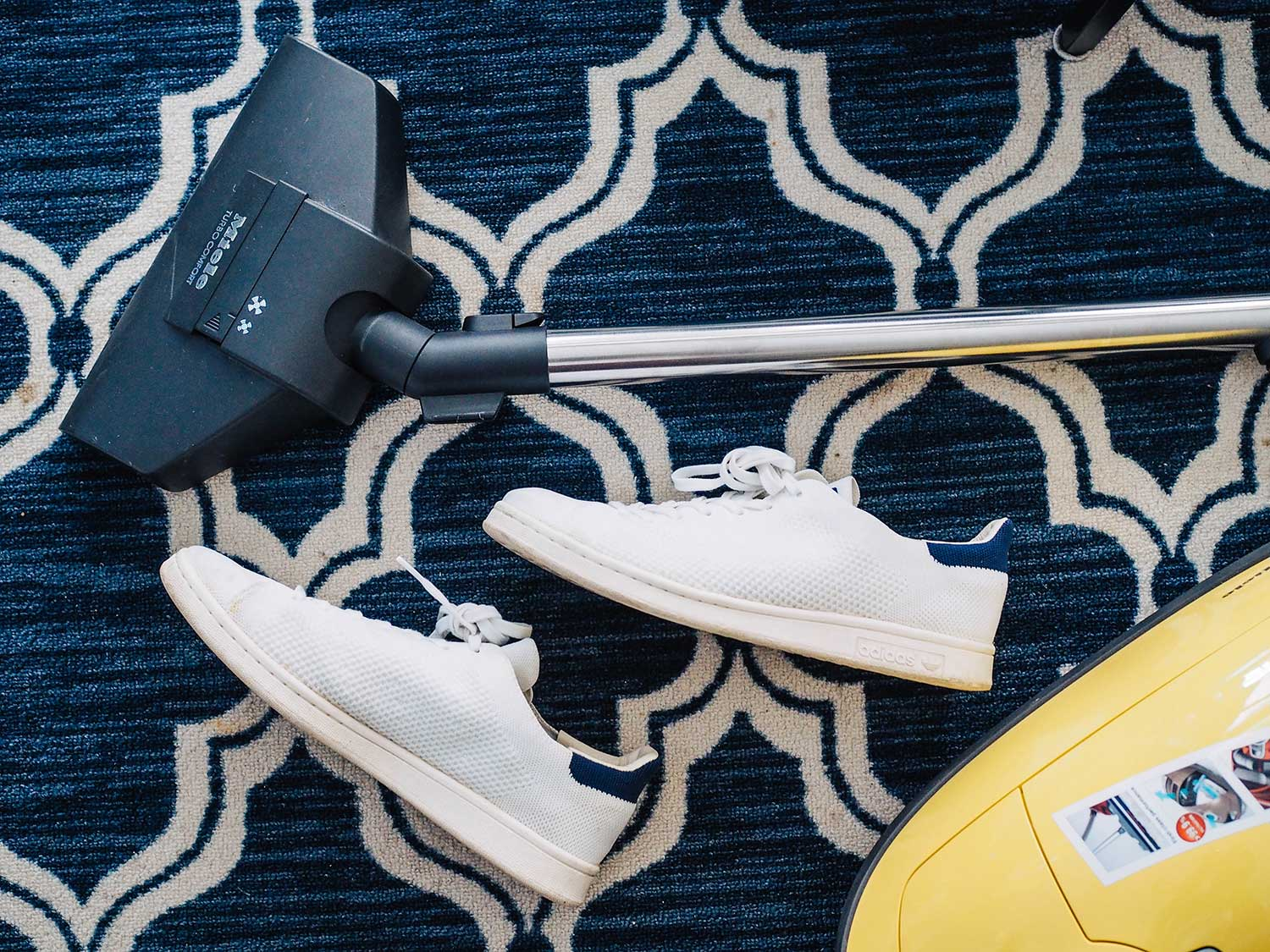 Cordless vacuum with white sneakers on rug.