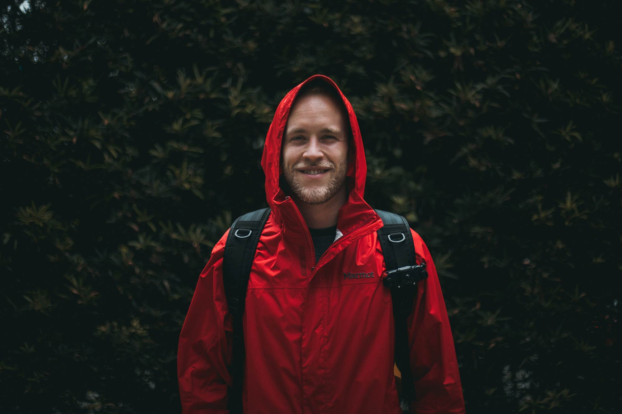 Man wearing a red rain jacket with hood.