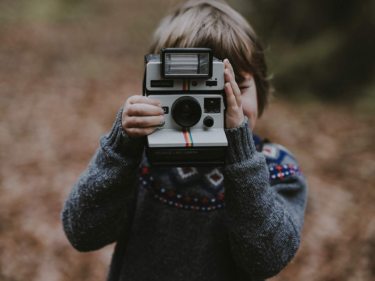 kid holding an instant camera