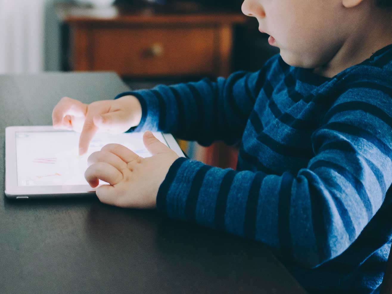 Kid playing on tablet.