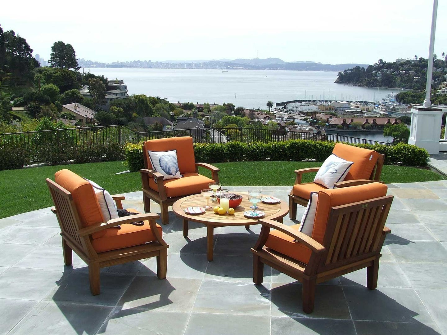 Outdoor patio furniture sitting outside by water.