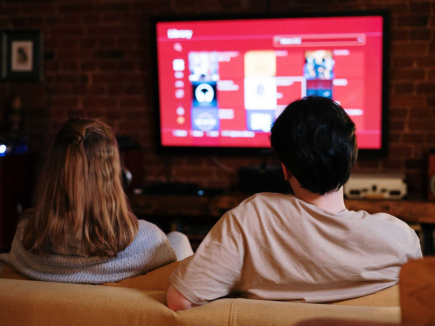 Man and woman watching movies on high-def TV.
