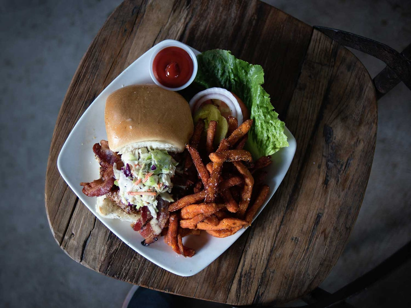 Burger and fries on plate on TV tray.