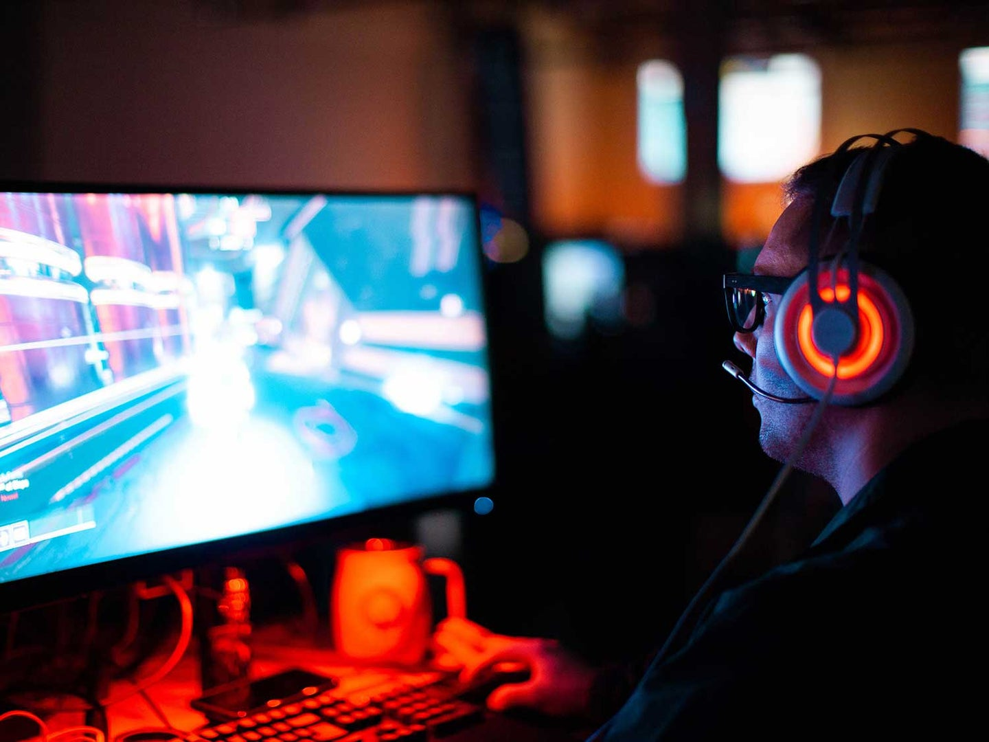 Man playing game on computer with surround sound gaming headset.