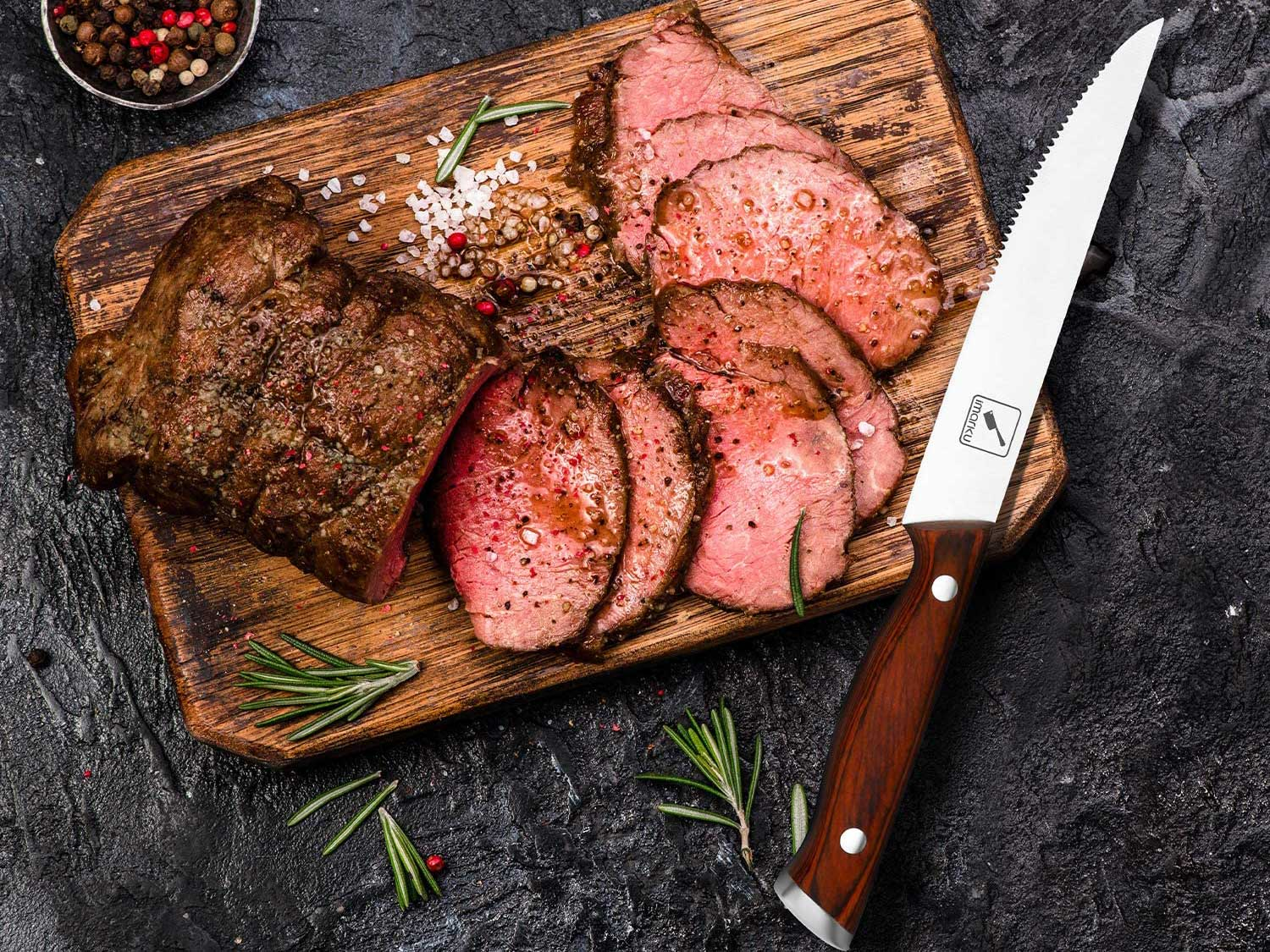 Steak knife on cutting board with sliced meat.