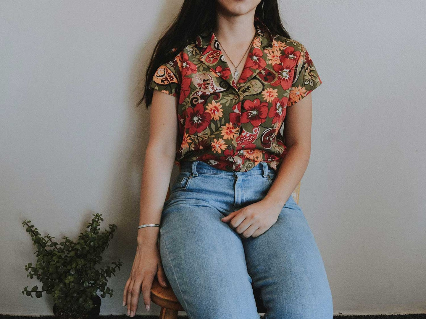 Woman wearing jeans and sitting beside green plant.