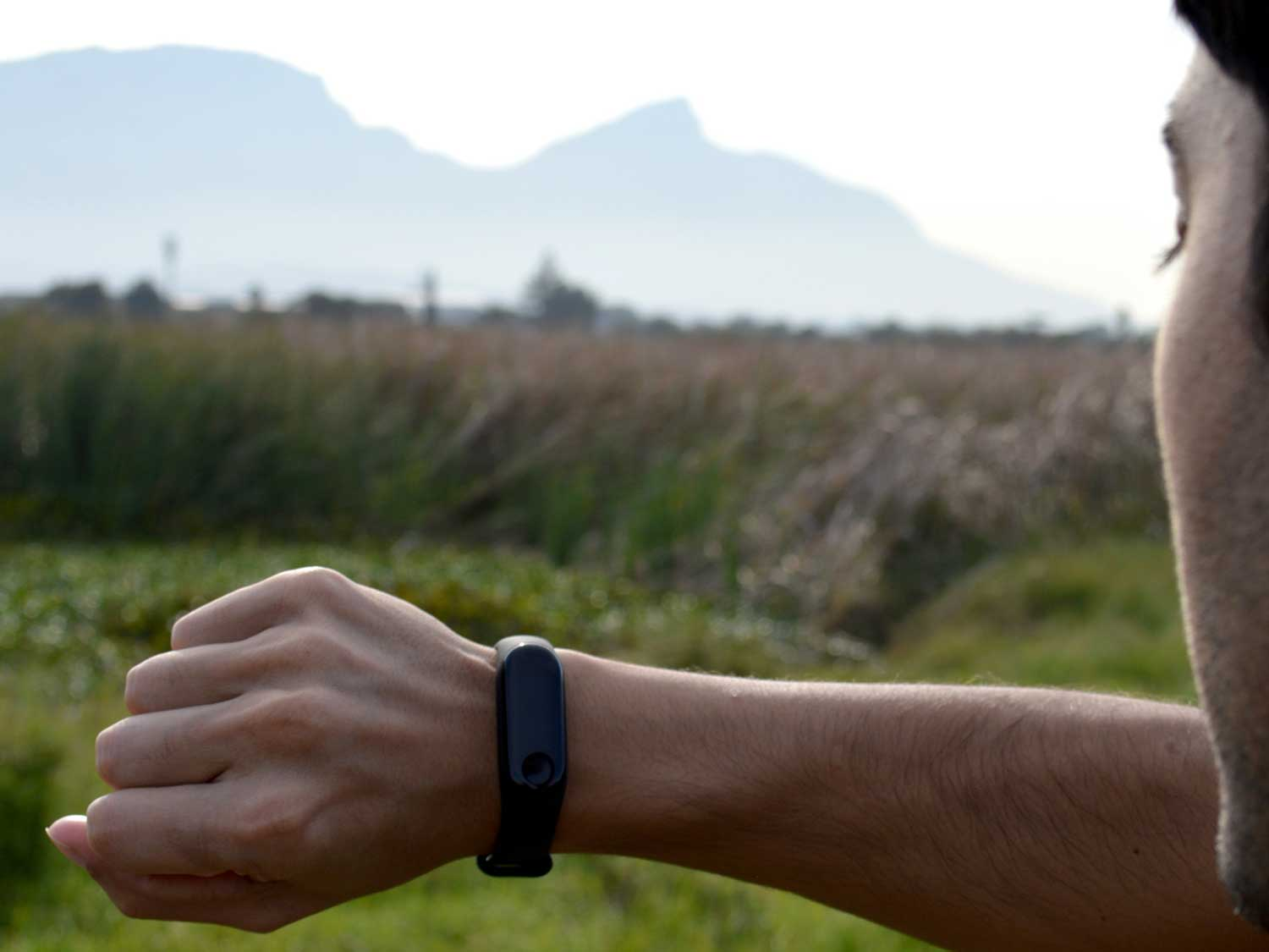 Man looking at fitness tracker while spending time outside in mountains.
