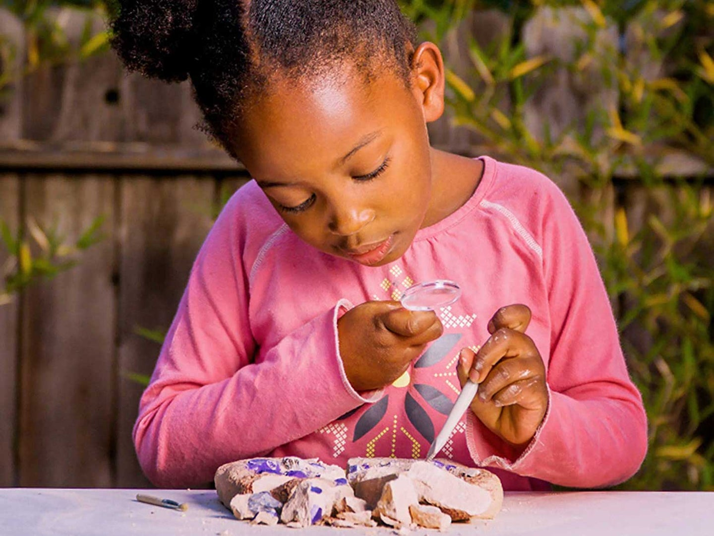 Girl digging in National Geographic dig kit.