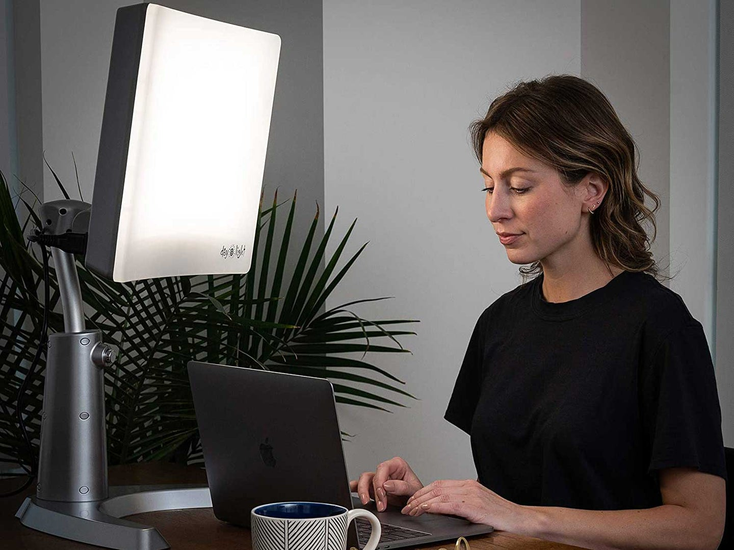 Woman doing work at laptop with light-therapy lamp.
