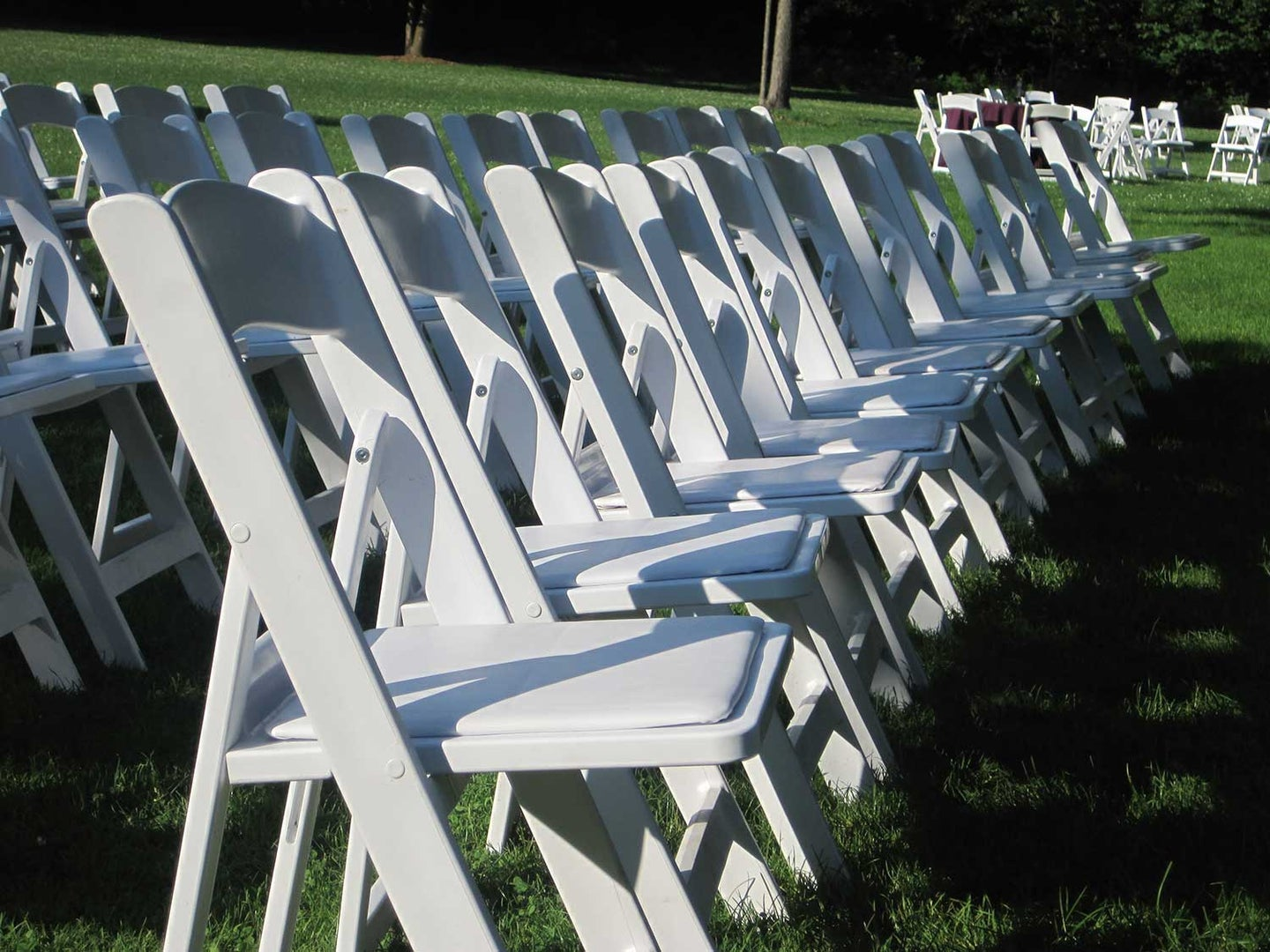 White folding chairs lined up on lawn.