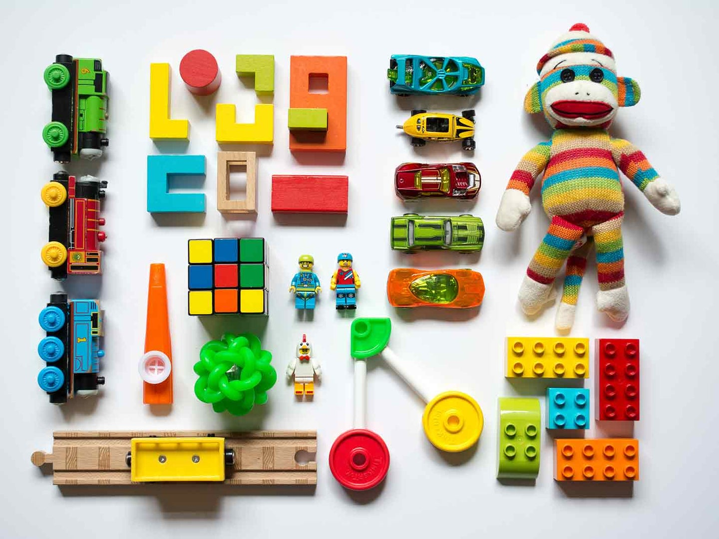 Kids toys spread out on white background.