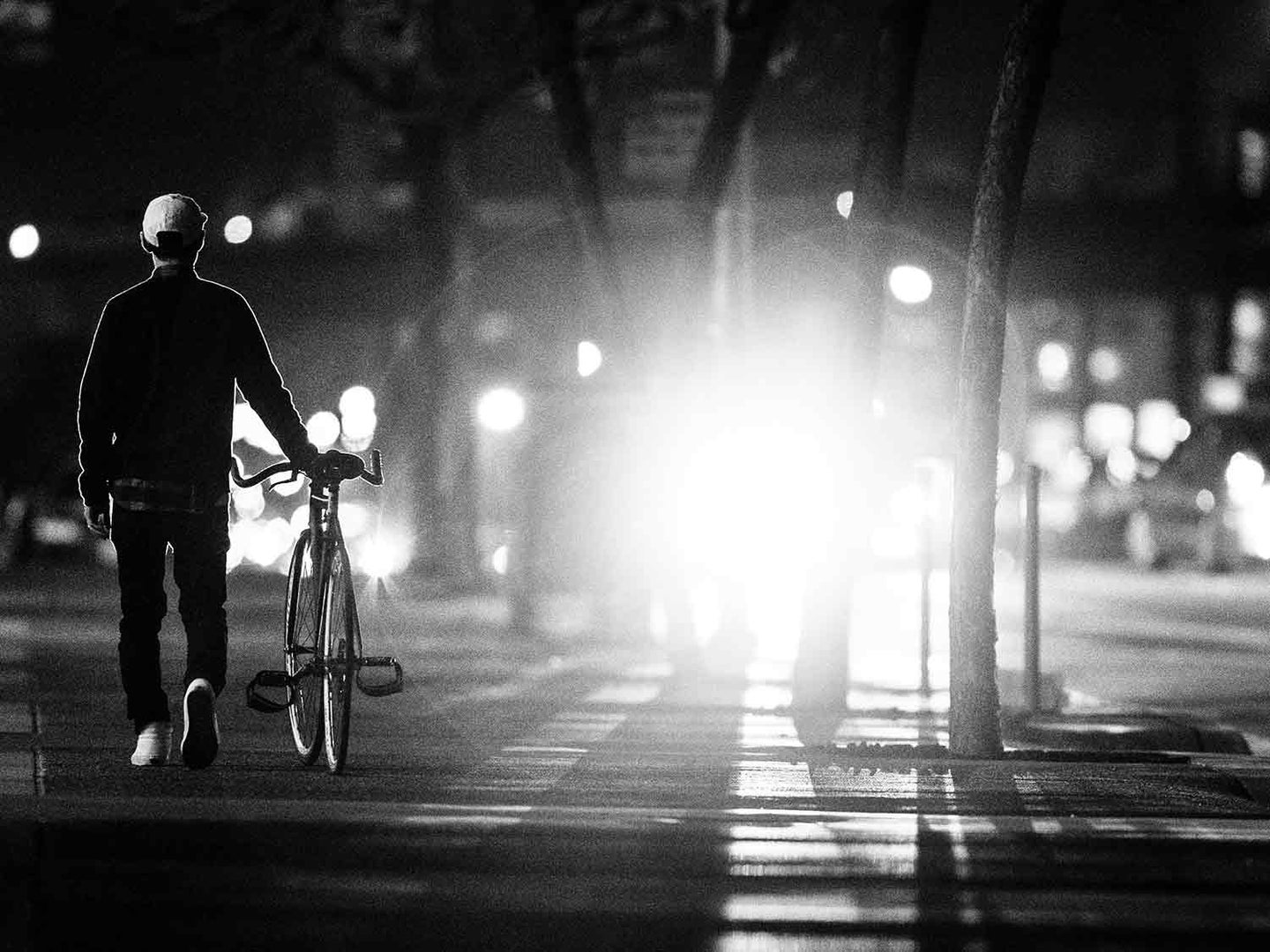 Man walking with bike at night with light.