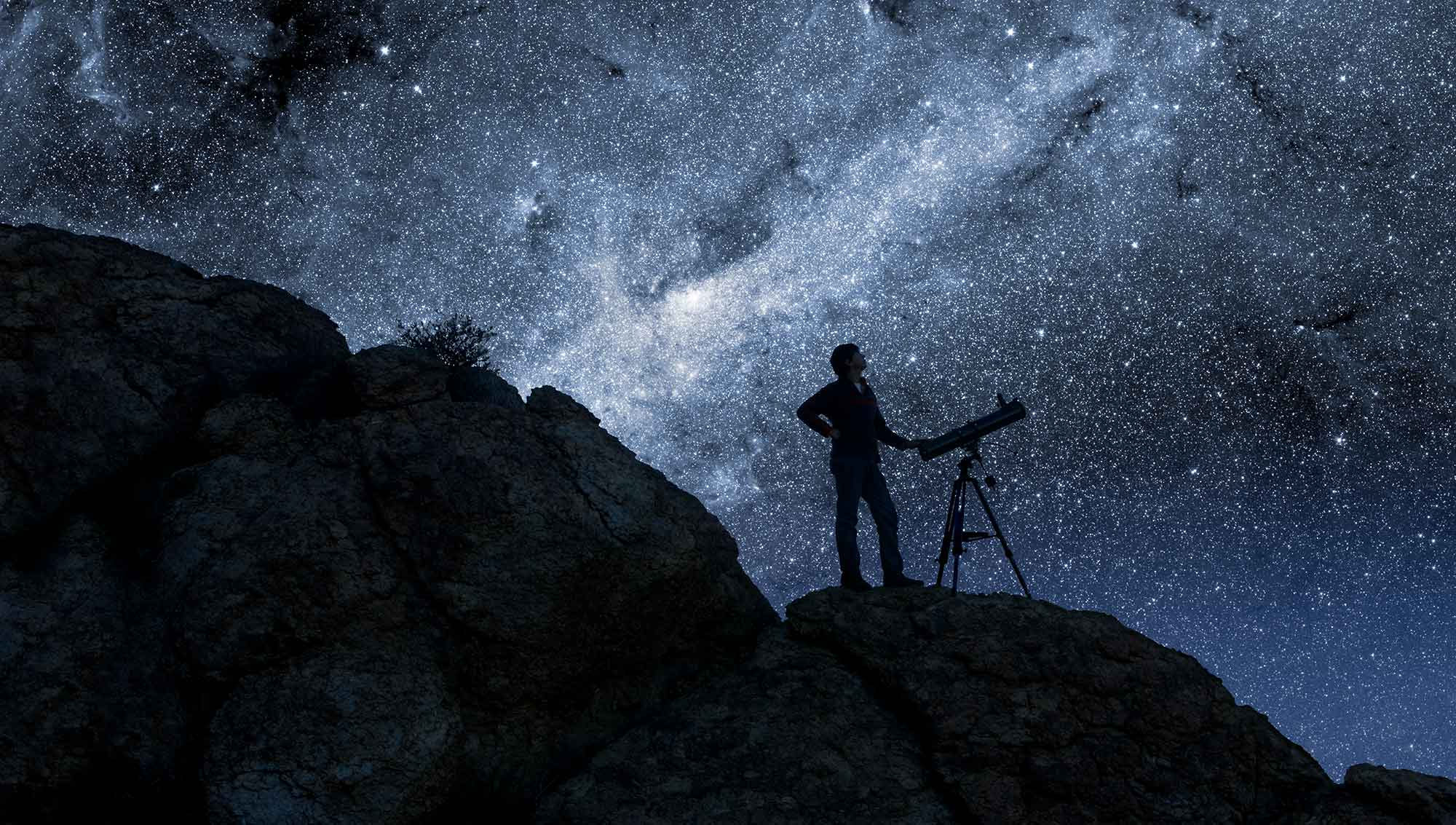 Person using a telescope under the stars.