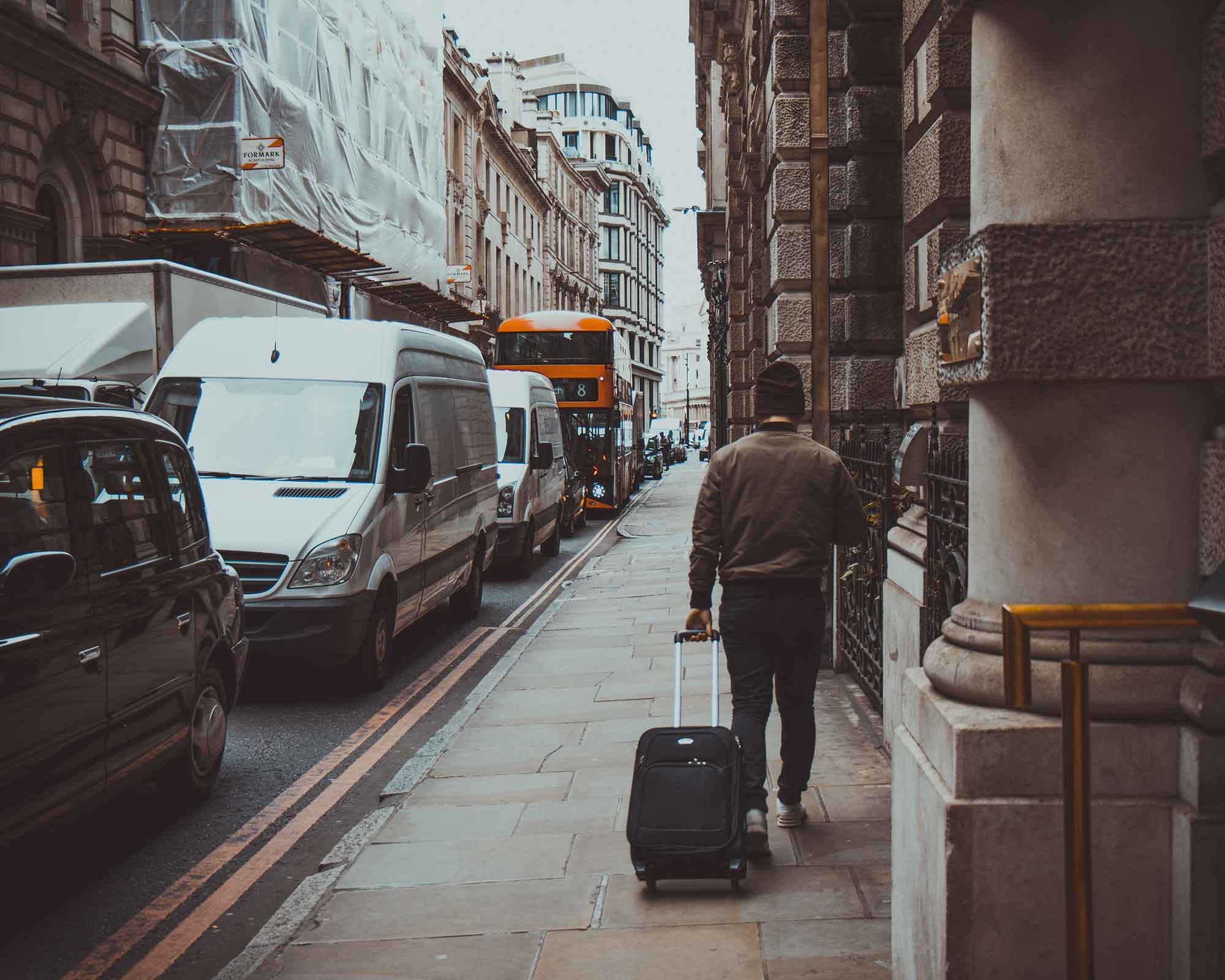 Person walking on street with luggage