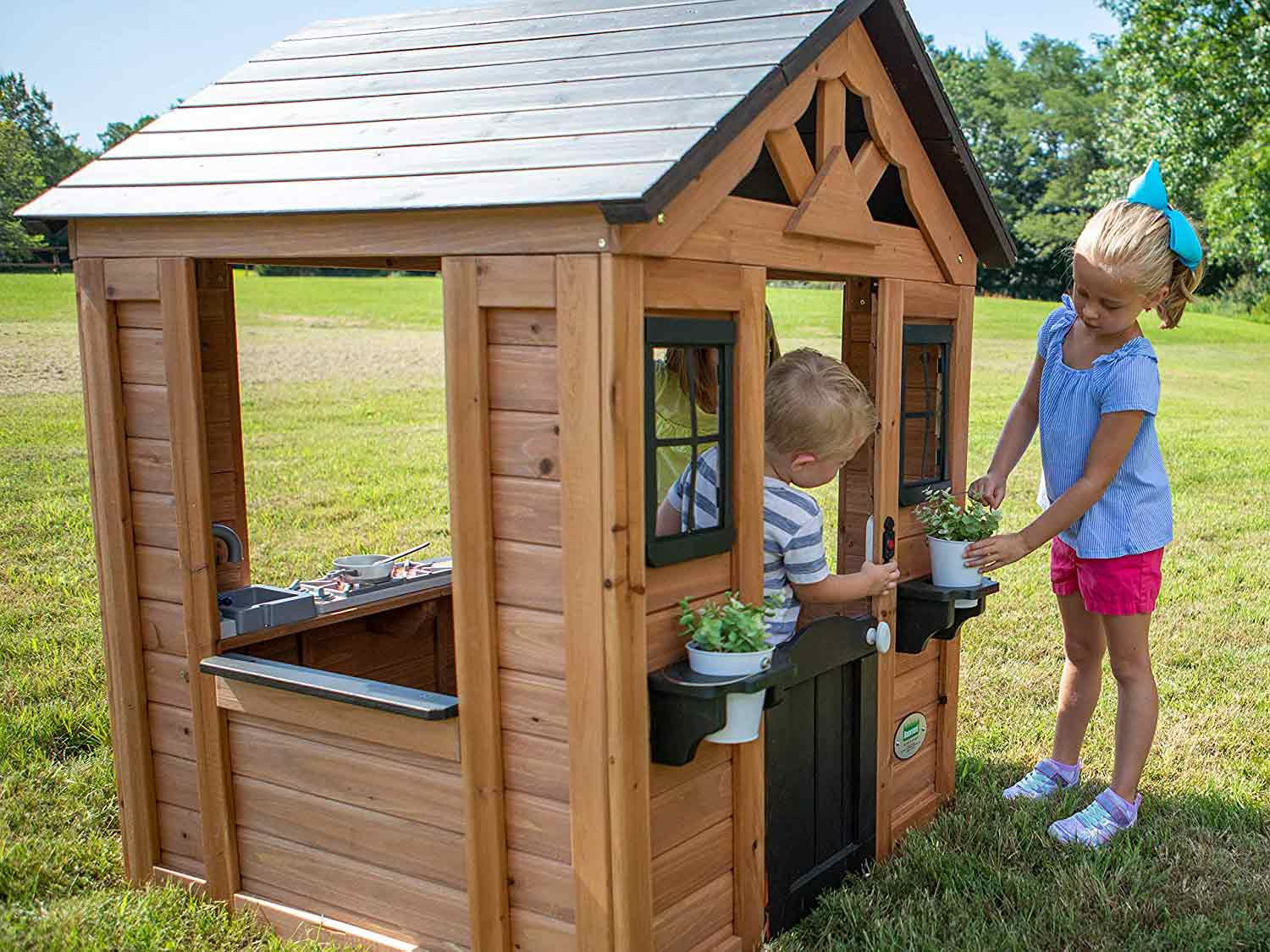 Kids playing in backyard playhouse