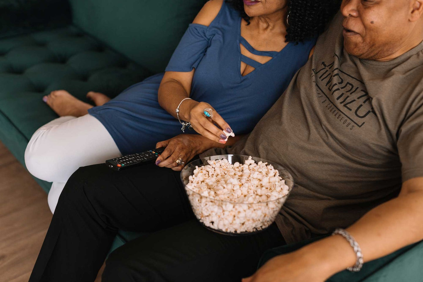 Two people eating popcorn on the couch