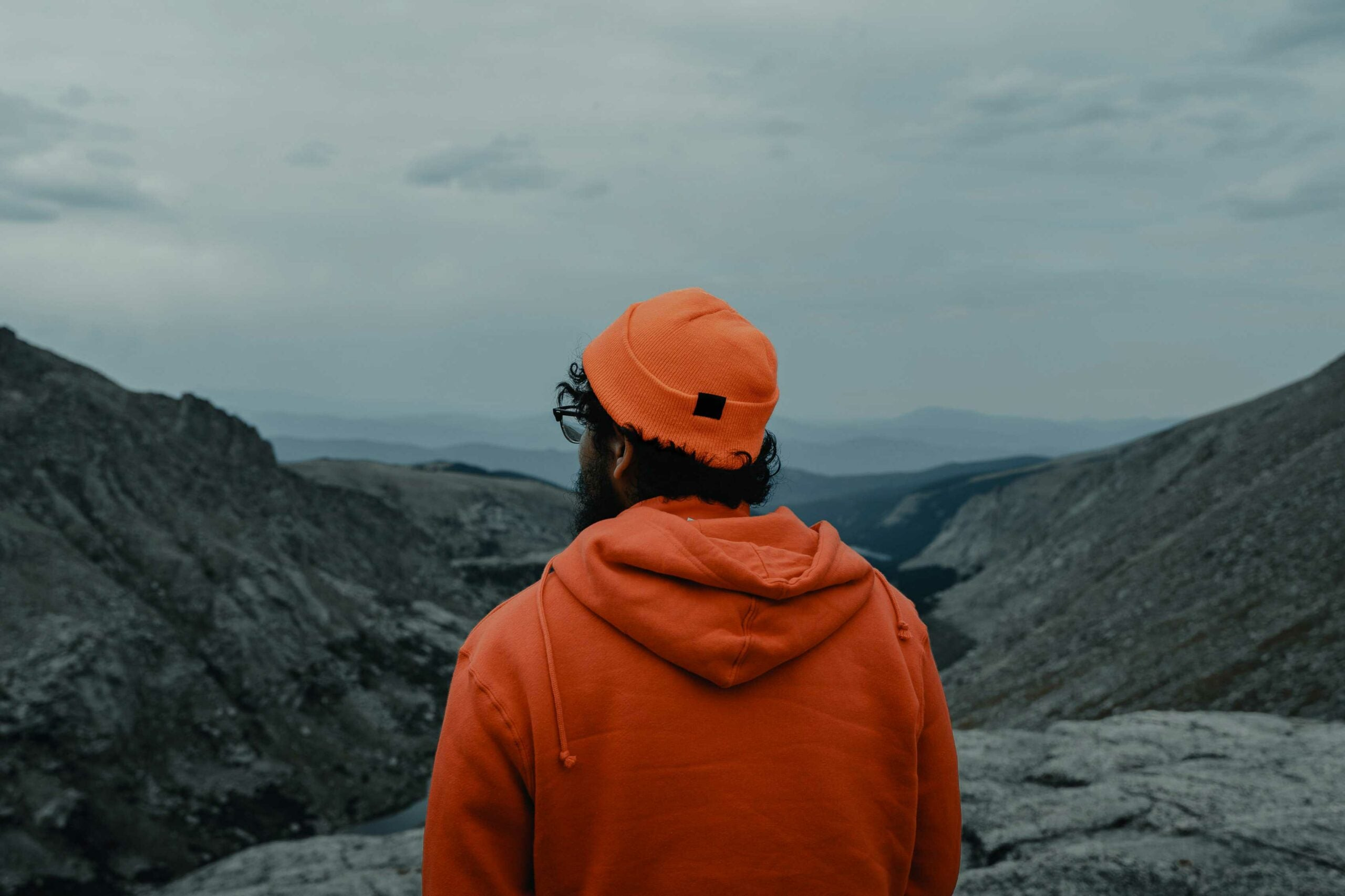 Men in an orange hat and sweatshirt staring over a mountaintop