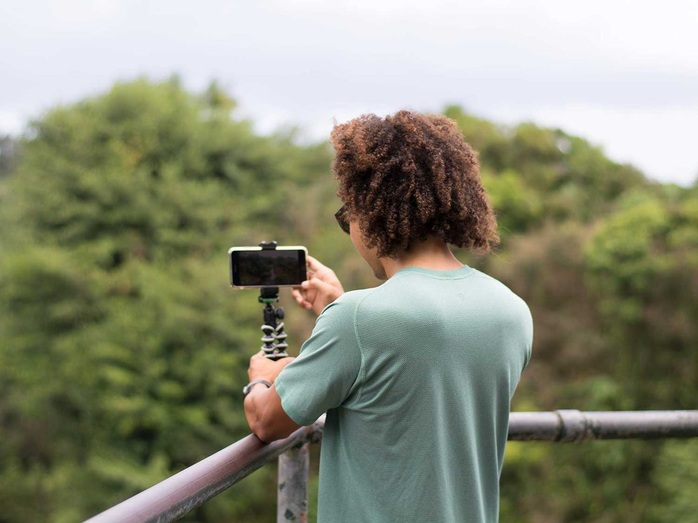 Man using smartphone tripod to take picture in forest.