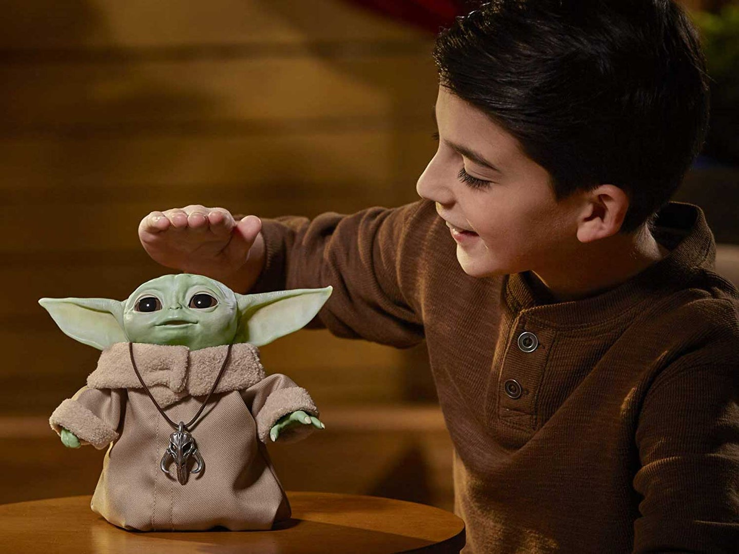 Boy playing with The Child Star Wars electronic pet.