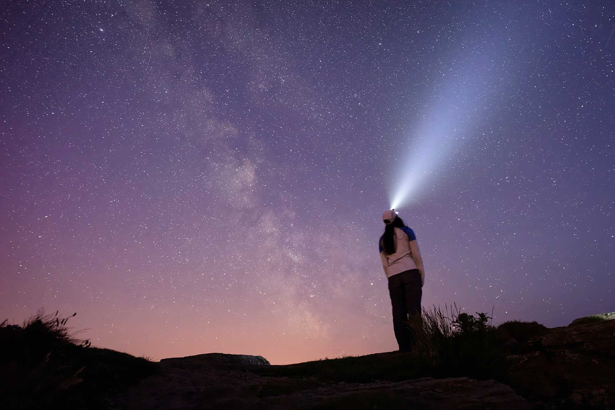 Person using a headlamp under the stars