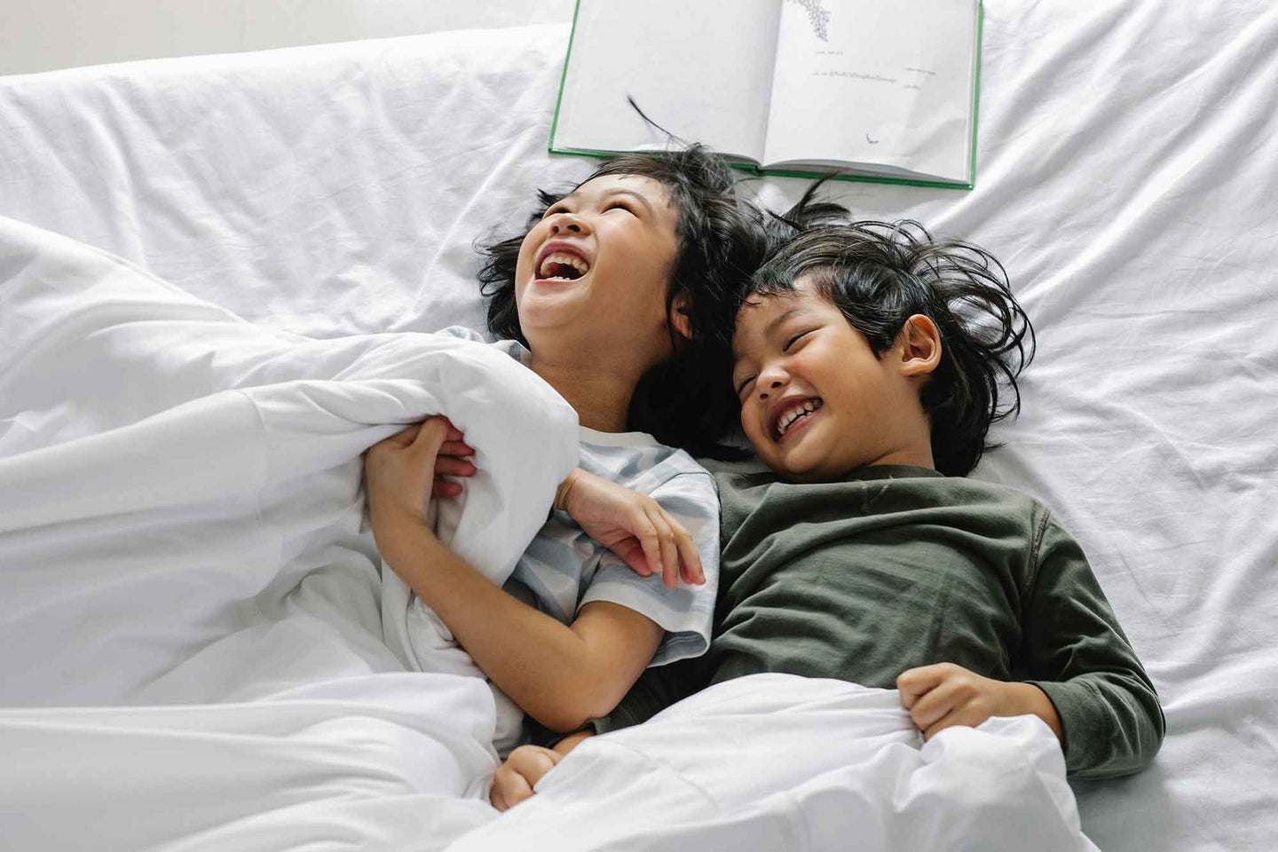 Two kids playing in bed