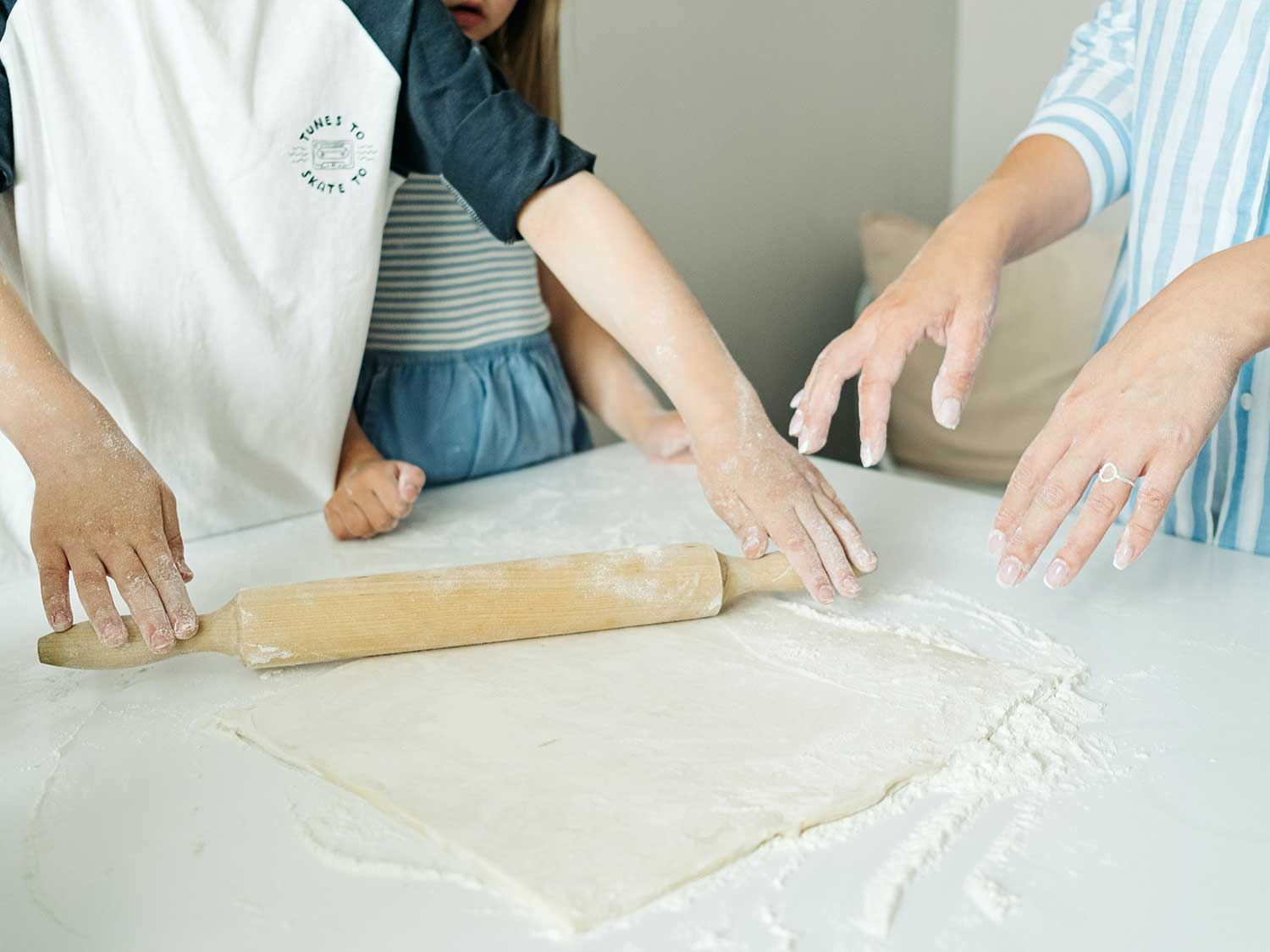 A family uses a rolling pin to flatten dough on kitchen counter.