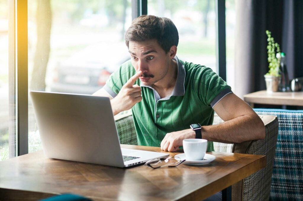 Man looking shocked at his laptop
