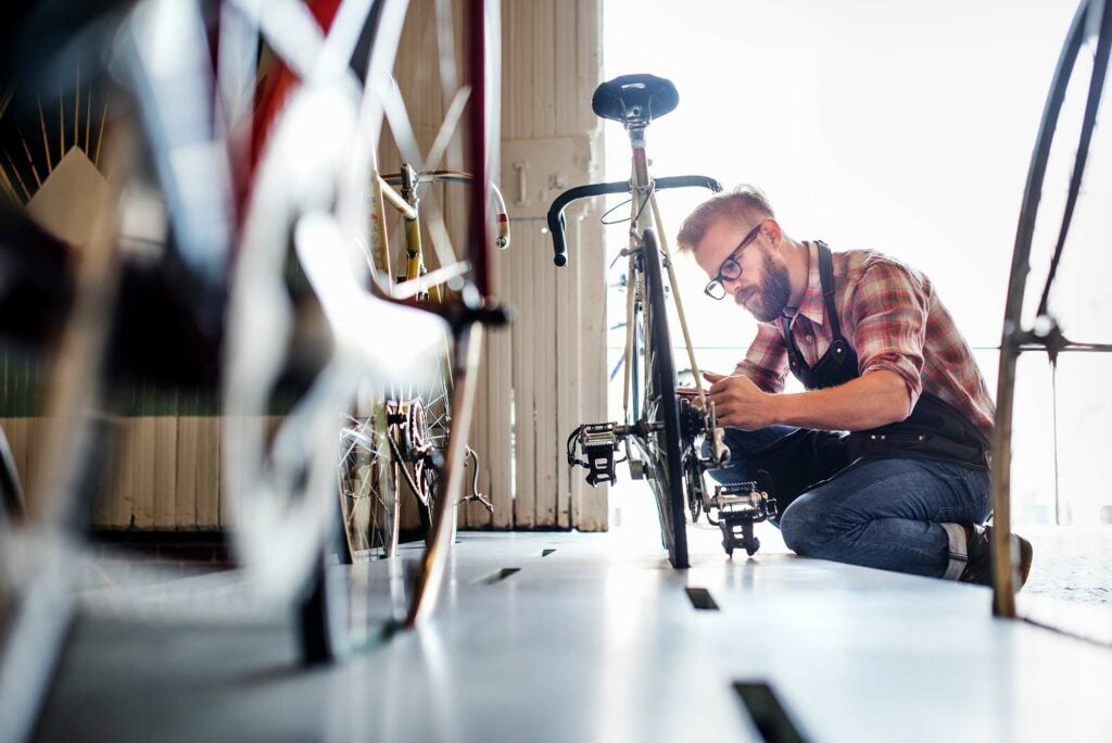 Hipster dude fixing a bike