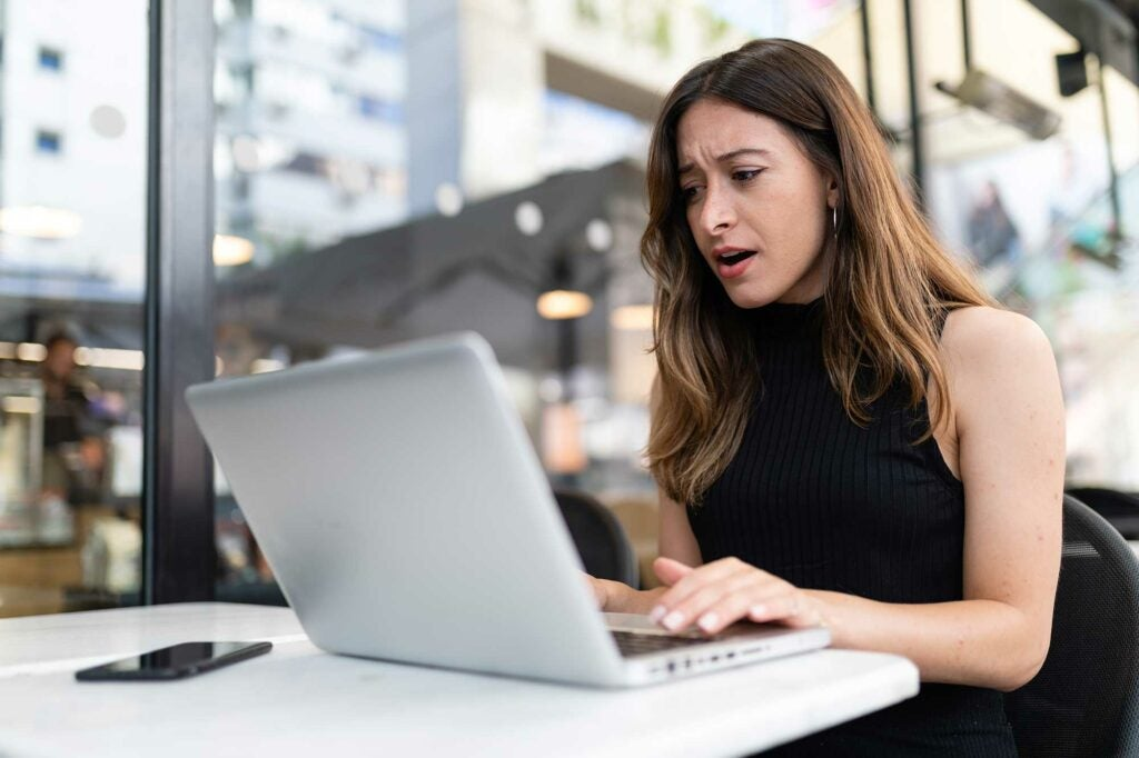 Woman looking shocked at a laptop
