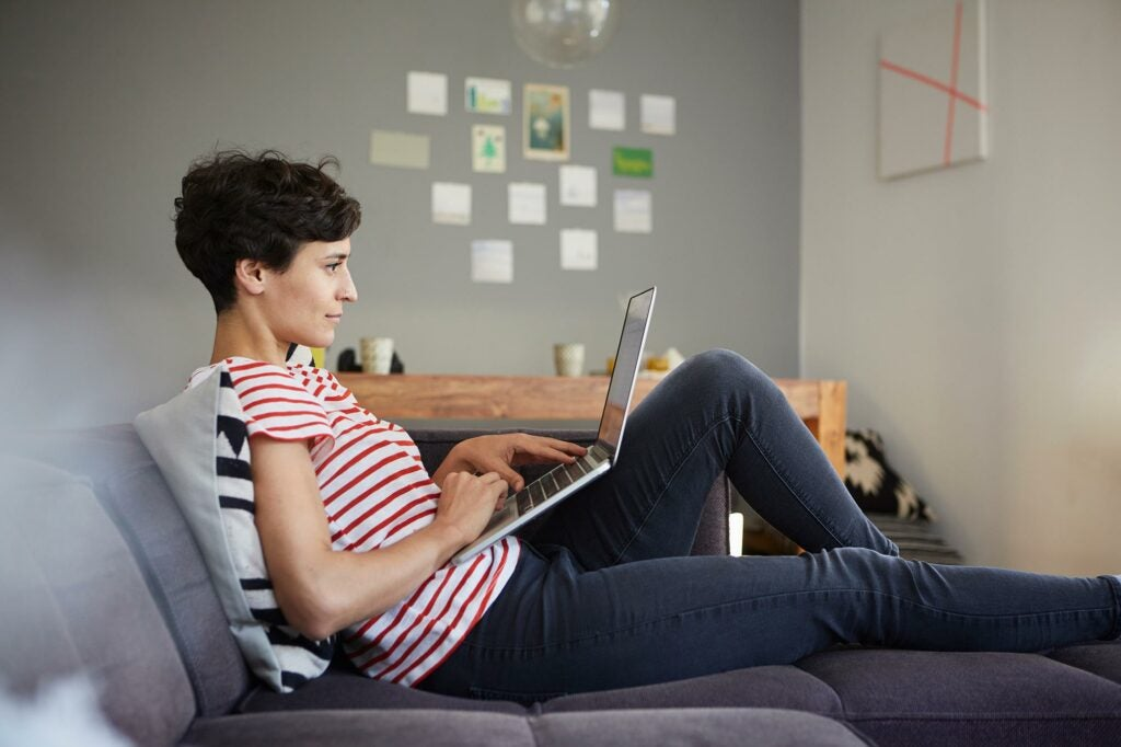 Woman on couch with her feet up looking at laptop