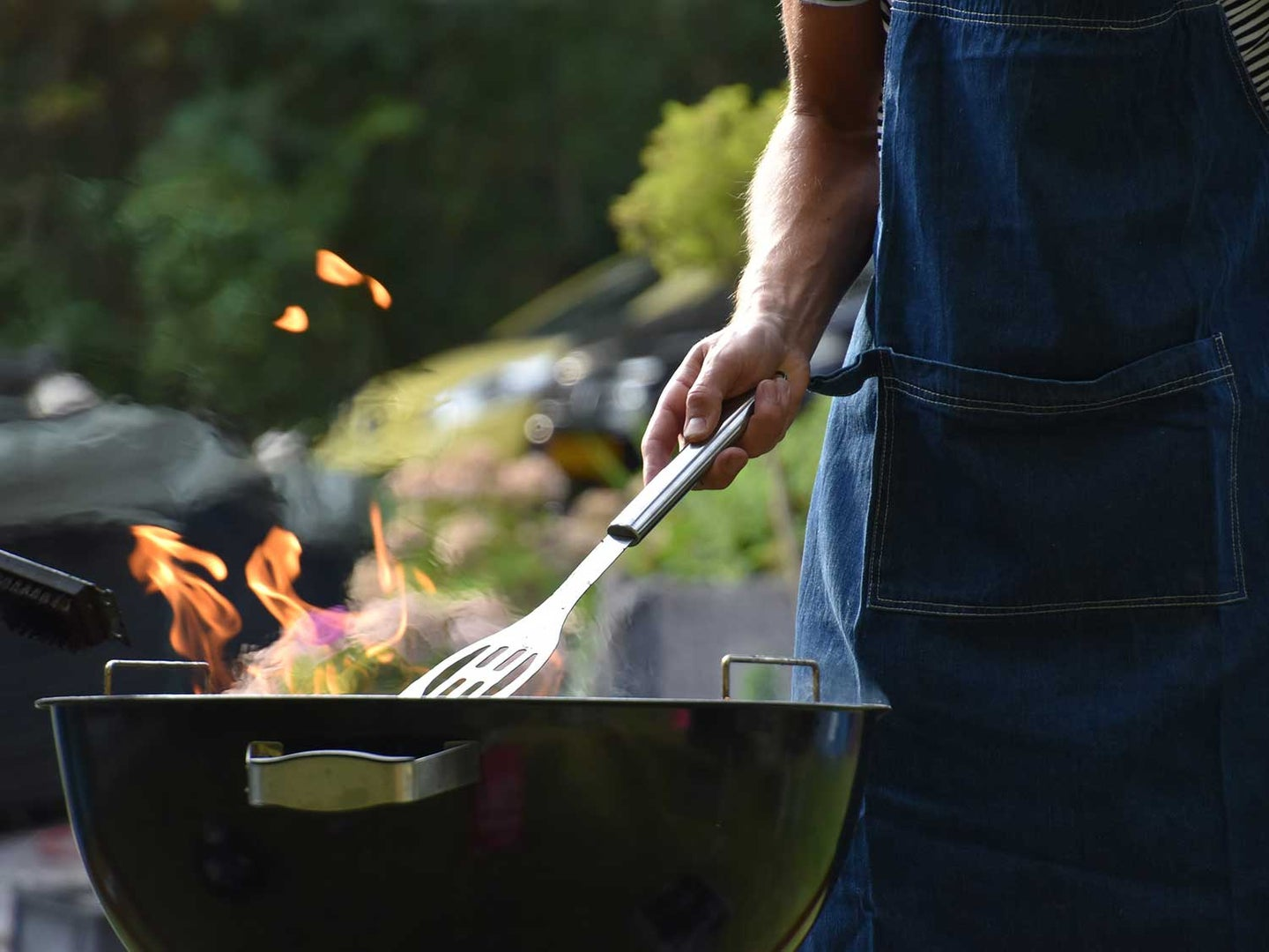 Man grilling on charcoal grill.