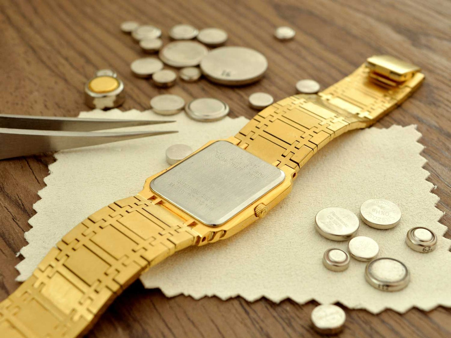Watch with watch batteries laid on table.