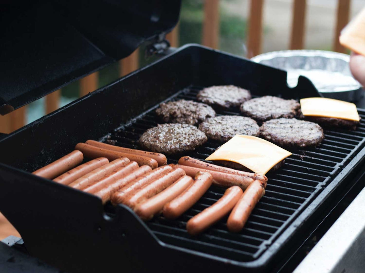 Grilling hamburgers and hot dogs.